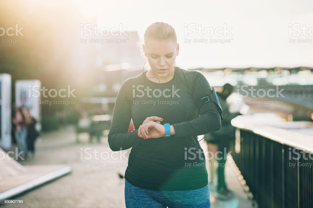 Sportswoman looking at her smart watch stock photo