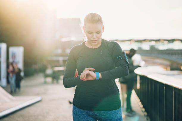 blick auf ihre smartwatch sportlerin - trainingsplan frauen stock-fotos und bilder