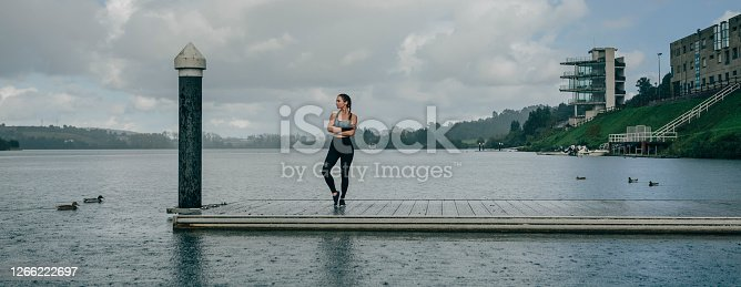 Young sportswoman looking at the lake from the pier under the rain