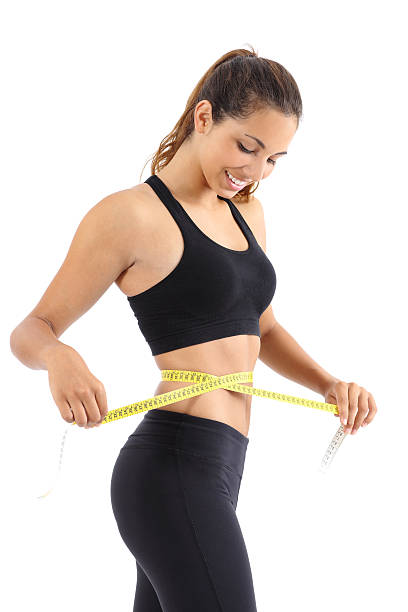 Sportswoman measuring her waist with a measure tape stock photo