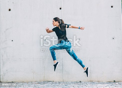 Sportswoman jumping in front of a wall outdoors.