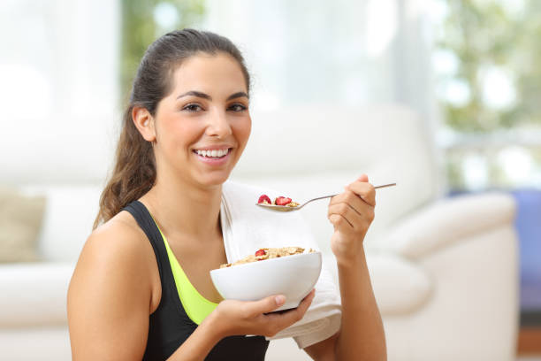 Sportswoman posing with cereals after sport at home stock photo