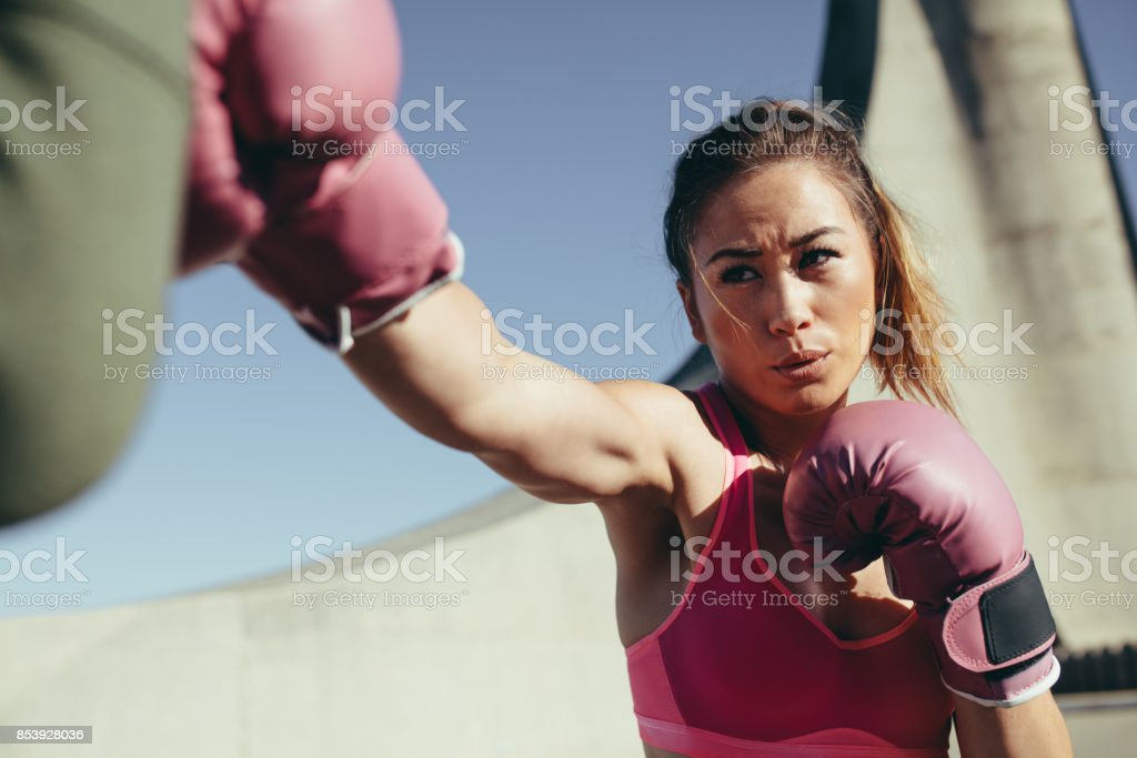 Sportswoman practicing boxing outdoors stock photo