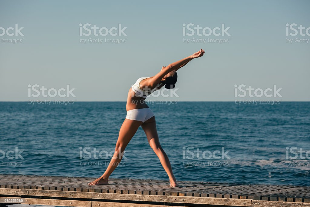 Sportswoman practicing yoga at the quay stock photo