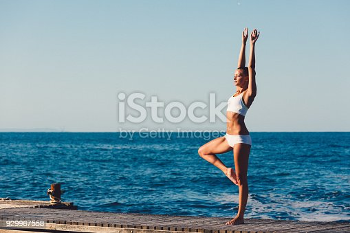 816941230 istock photo Sportswoman practicing yoga at the seaside 929967558