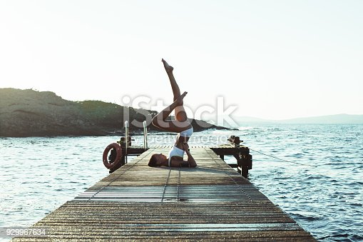 816941230istockphoto Sportswoman practicing yoga at the seaside 929967634
