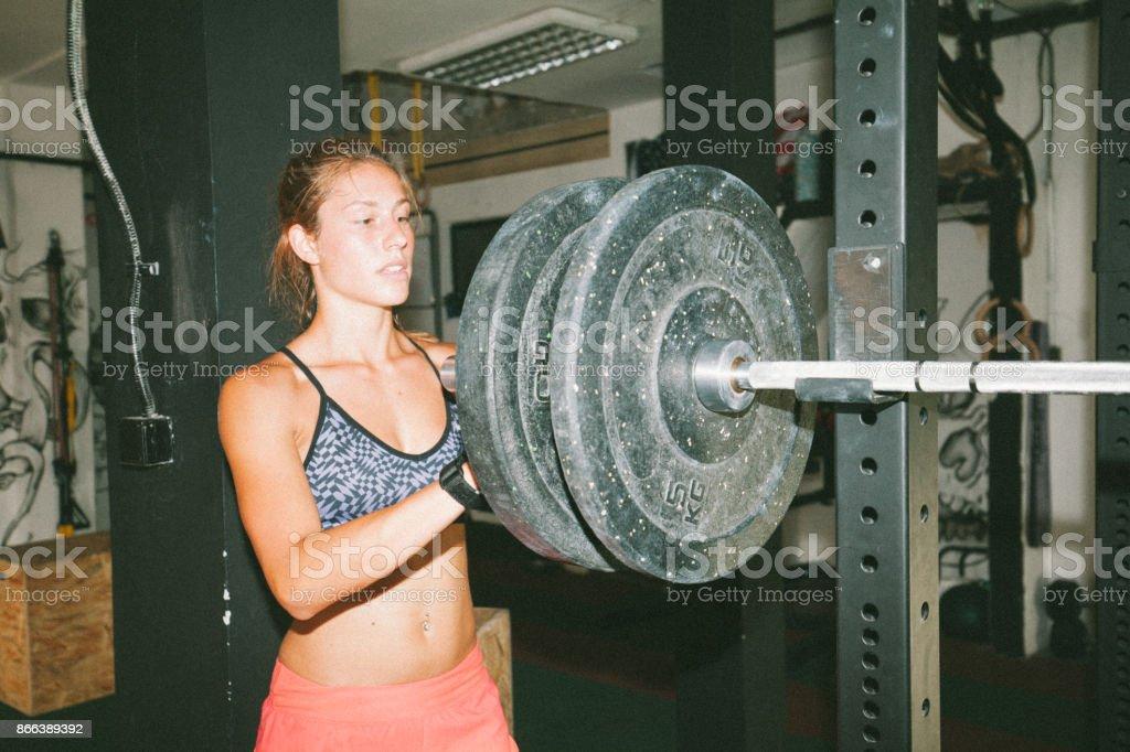 Sportswoman preparing barbell for exercise stock photo