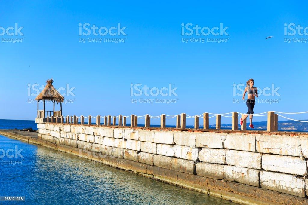 Sportswoman runing on stone wall stock photo