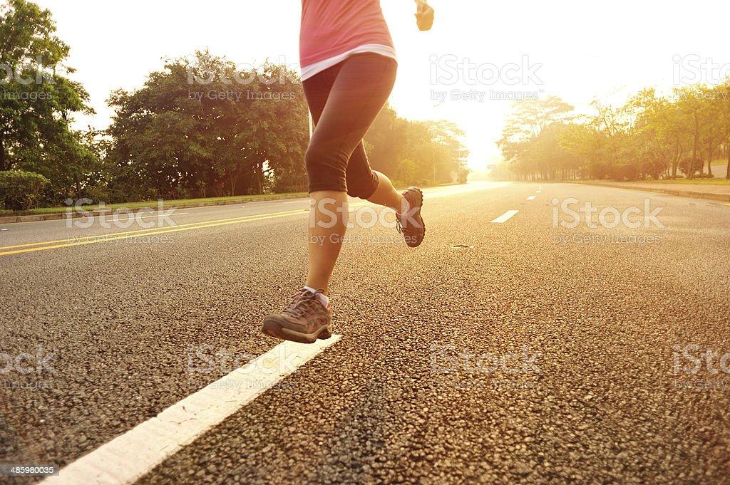 Sportswoman running along driveway stock photo