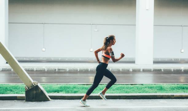 Sportswoman running in the city stock photo