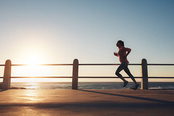 Sportswoman running on a road by the sea Image of fit sportswoman jogging on a road by the sea during evening. Female runner training at sunset. promenade stock pictures, royalty-free photos & images