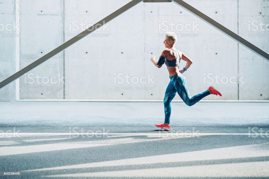 Sportswoman running outdoors at industrial zone stock photo