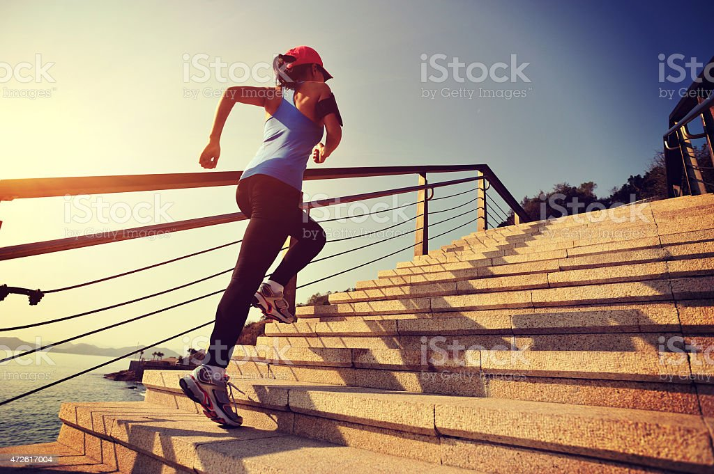 Sportswoman running up on stone stairs stock photo