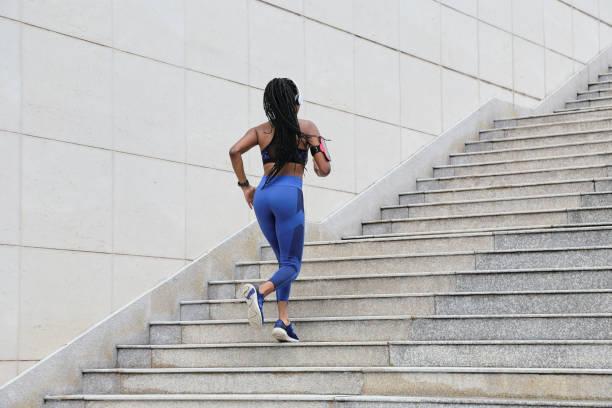 Sportswoman running up the stairs stock photo