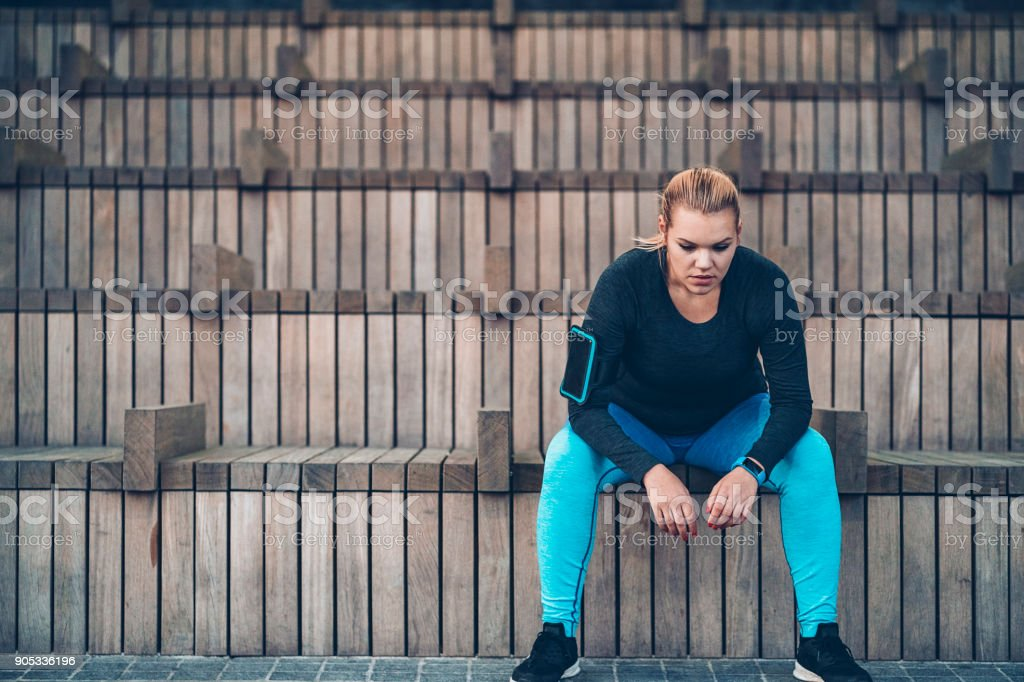 Sportswoman sitting alone stock photo