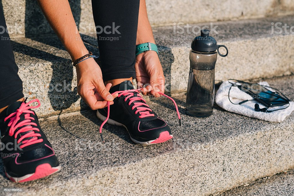 Sportswoman sitting on stairs adjusting sport shoes in early morning stock photo