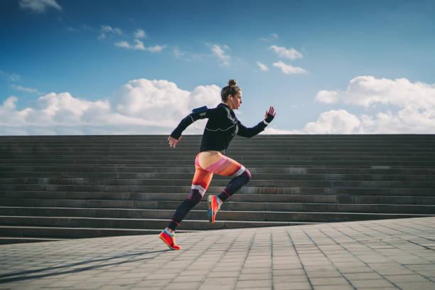 sportlerin sprintet in der stadt - joggerin stock-fotos und bilder