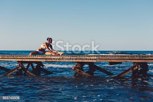 816941230istockphoto Sportswoman stretching at beach holiday 933743326