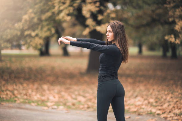Sportswoman stretching her both arms in the woods stock photo