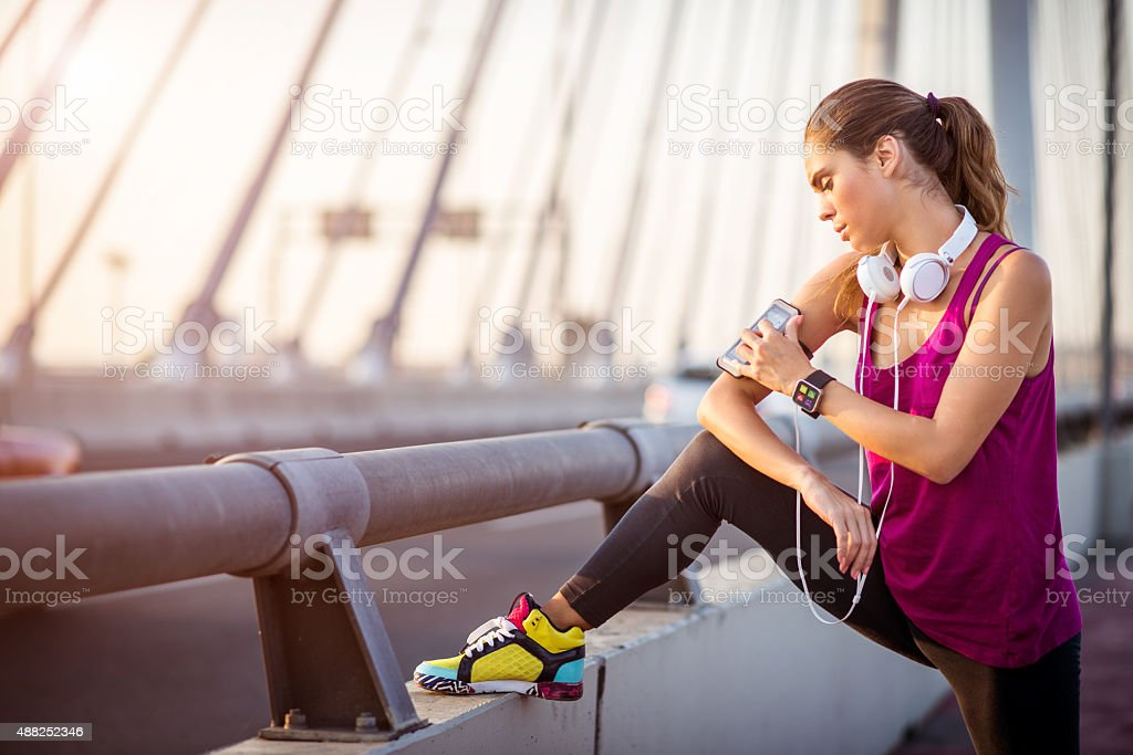 Sportswoman stretching leg on the bridge after cardio session stock photo