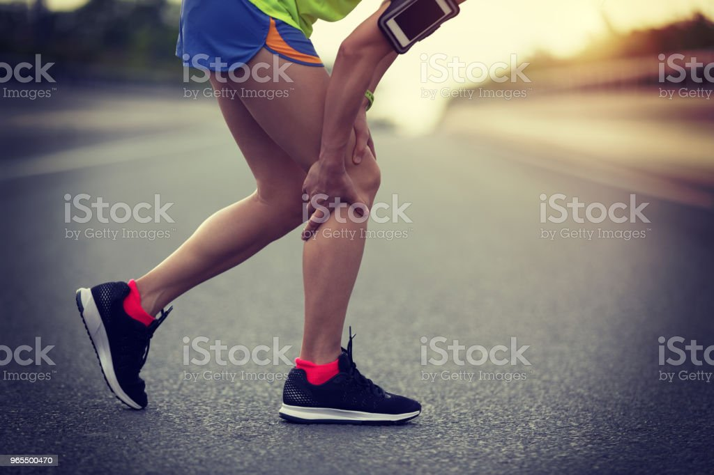 sportswoman suffering from knee pain while running on city road – zdjęcie