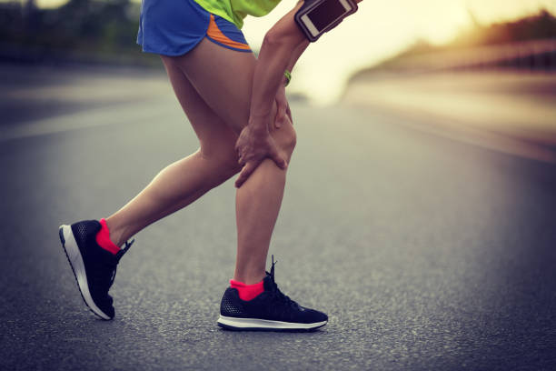sportswoman suffering from knee pain while running on city road stock photo