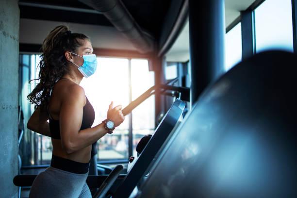 sportvrouw opleiding op loopband in de sportschool en het dragen van gezichtsmasker om zichzelf te beschermen tegen coronavirus tijdens de wereldwijde pandemie van covid-19 virus. - sportschool stockfoto's en -beelden