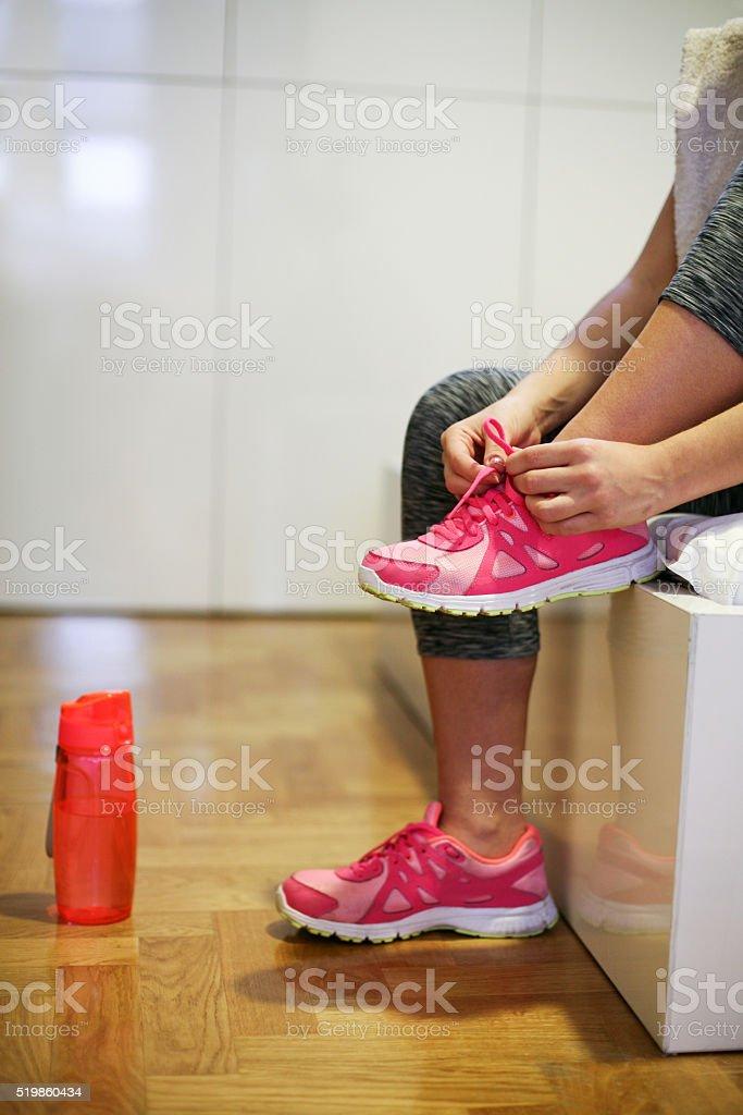 Sportswoman tying laces on sneakers. stock photo