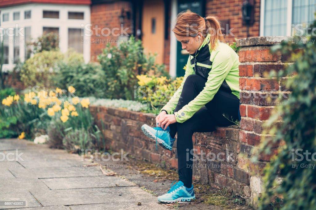 Sportswoman tying shoelaces before workout stock photo