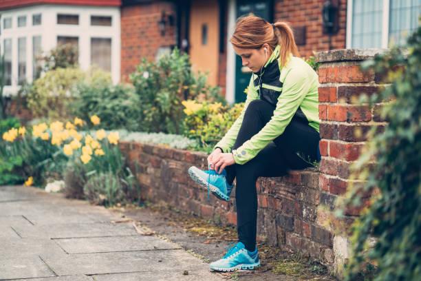 sportlerin, die schnürsenkel zu binden, vor dem training - schuhe auf englisch stock-fotos und bilder