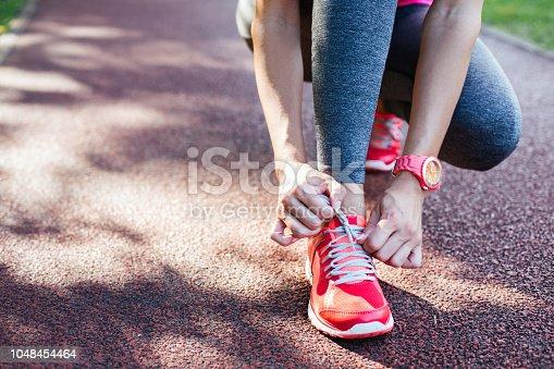 Closeup of runner tying shoelaces before running