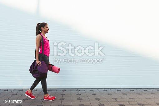 istock sportswoman walking in the city 1048457572