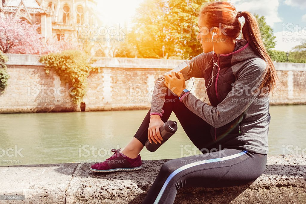 Sportswoman with armband resting at the Seine river stock photo