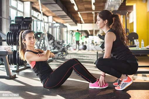 istock Sportswoman with assistance of her friend doing sit-ups in gym. 635742998