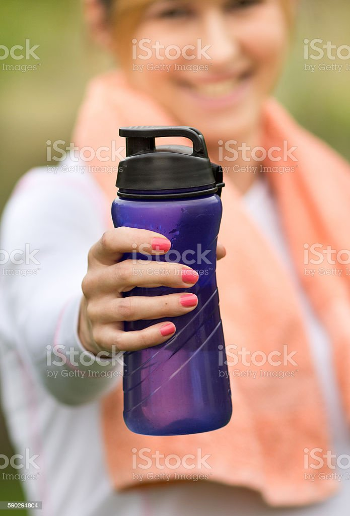 Sportswoman with bottle resting in park royaltyfri bildbanksbilder