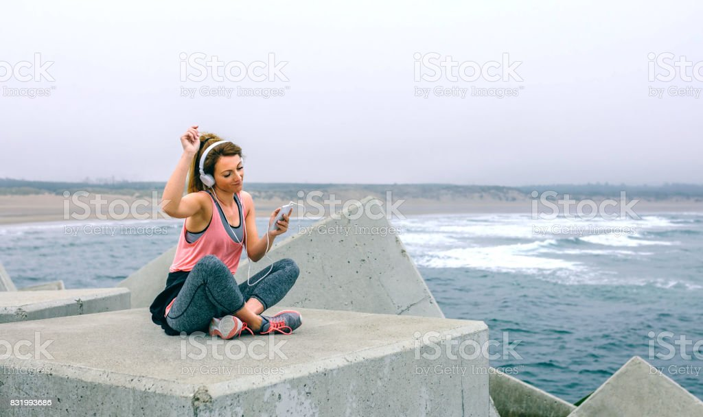 Sportswoman with headphones sitting and dancing stock photo