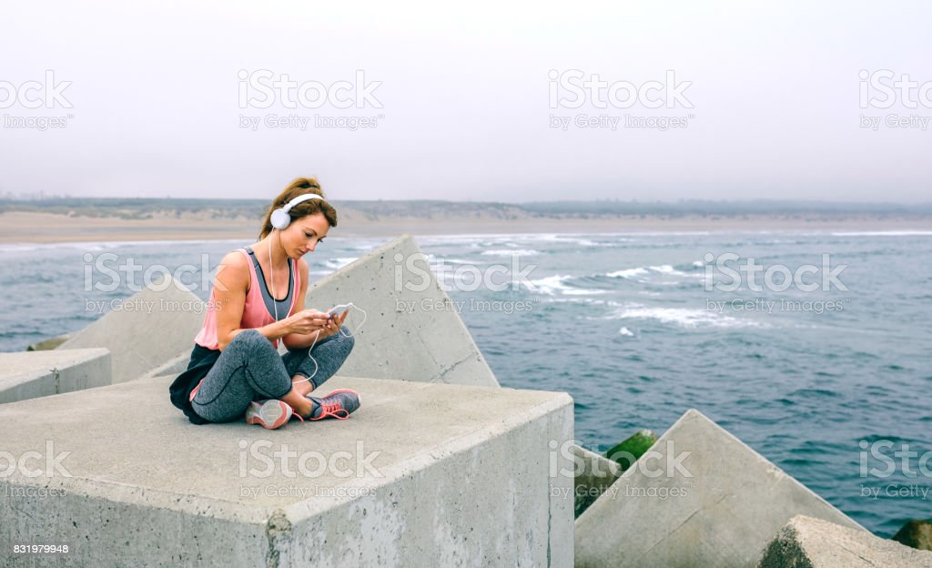 Sportswoman with headphones sitting stock photo