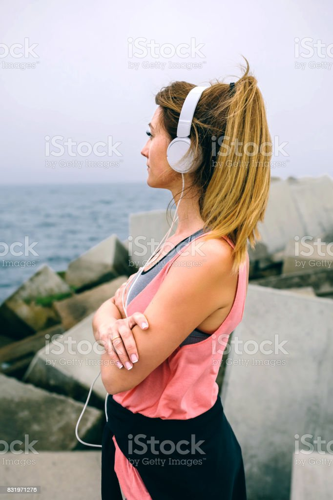 Sportswoman with headphones watching the sea stock photo