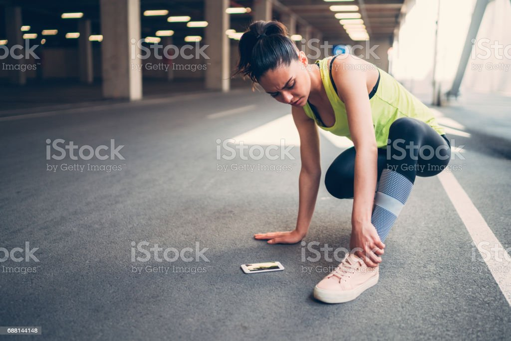 Sportswoman with injured ankle stock photo