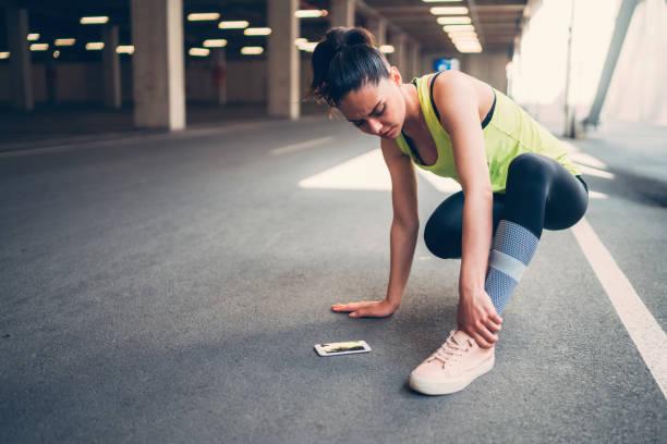 sportswoman with injured ankle - caviglia foto e immagini stock