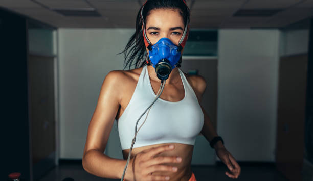 Sportswoman with mask running on treadmill in gym stock photo