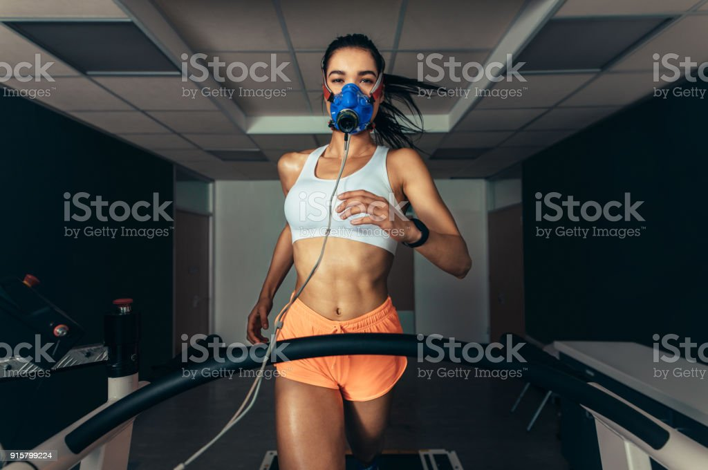 Sportswoman with mask running on treadmill stock photo