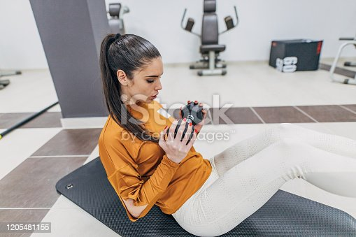 1035512048istockphoto Sportswoman working out with dumbbell on exercise mat 1205481155
