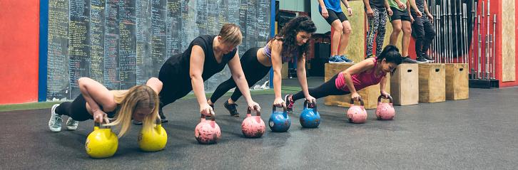 istock Sportswomen training with kettlebells and sportsmen doing box jumps 1184347958