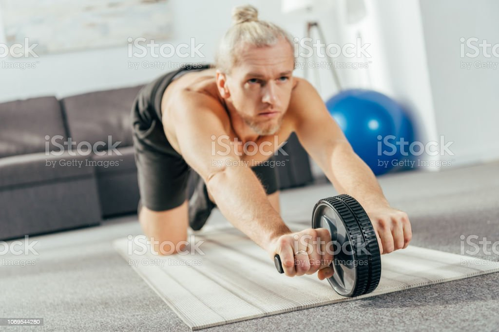 sporty adult man exercising with abs roller at home stock photo
