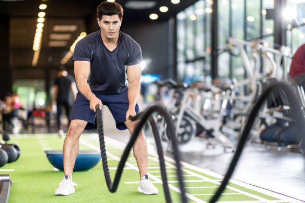 Sporty asian man exercising with battle ropes at the gym on green floor. Strong male determine with her indoor workout for stamina and building muscular body. Athlete battle rope workout concept. stock photo