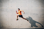 istock Sporty Asian Mid man running and jumping against shutter. Health and fitness concept. 1161313454