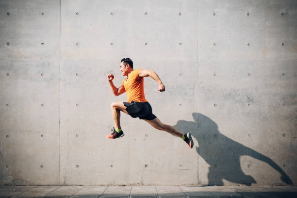 Sporty Asian Mid man running and jumping against shutter. Health and fitness concept. Men, Running, Jumping, Asian and Indian Ethnicities, East Asian Ethnicity, Mid Adult mid air stock pictures, royalty-free photos & images