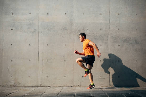 Sporty Asian Mid man running and jumping against shutter. Health and fitness concept. stock photo