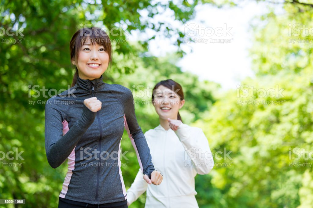 sporty asian woman running in park stock photo